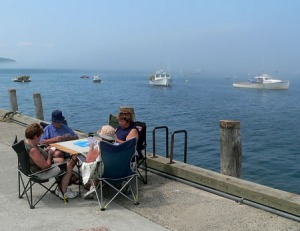 Card players on the town pier, summer in Bar Harbor.